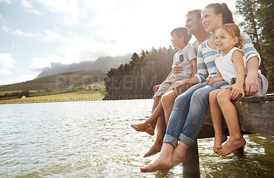 Buy stock photo Side view of a smiling family fo four sitting on the edge of a pier and admiring the lake