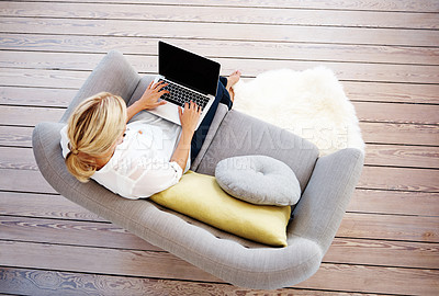 Buy stock photo An upper view of a blonde woman sitting on her couch working on her laptop