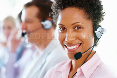 Buy stock photo Female customer service representative smiling with team in blur background