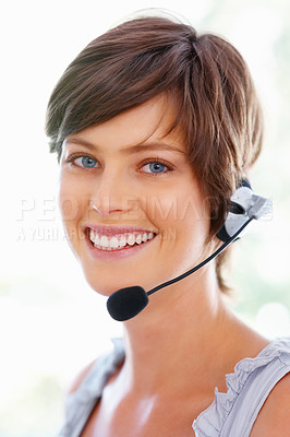 Buy stock photo Happy young call center executive using headphones and smiling