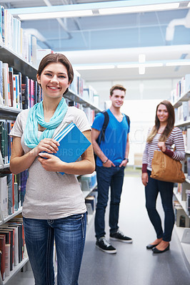 Buy stock photo Shot of three young adults smiling in a library