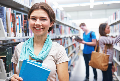 Buy stock photo Shot of three students in the library gathering books