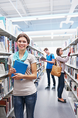 Buy stock photo Shot of three learners in a library doing research