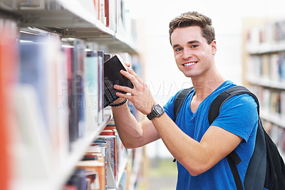 Buy stock photo Shot of a young man looking pleased as he finds the book he wants