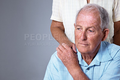 Buy stock photo Studio shot of an elderly man with his wife's hand on his shoulder