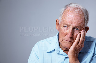 Buy stock photo Studio shot of a sad looking elderly man with his hand on his chin