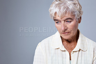 Buy stock photo Studio shot of a sad-looking elderly woman against a gray background
