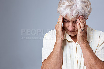 Buy stock photo Studio shot of a senior woman with a headache against a gray background
