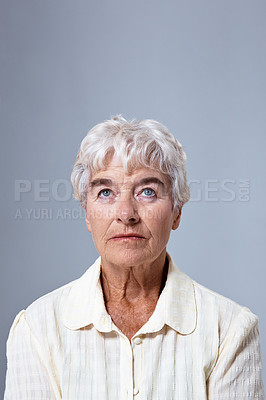 Buy stock photo Studio shot of an elderly womman looking up at copyspace against a gray background