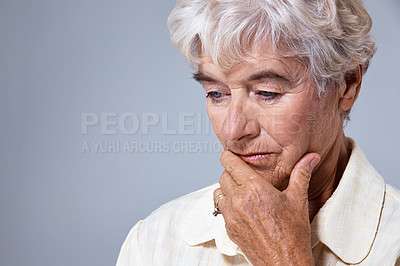 Buy stock photo Closeup studio shot of a depressed elderly woman against a gray background