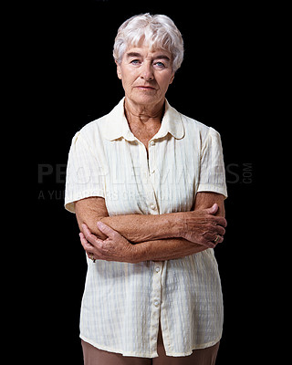 Buy stock photo Studio portrait of an elderly woman standing with her arms crossed isolated on black