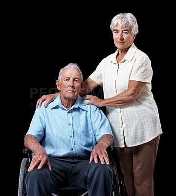 Buy stock photo Studio portrait of an elderly man in a wheelchair with his wife standing at his side isolated on black