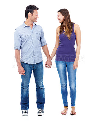 Buy stock photo Shot of a down to earth couple holding hands and smiling at each other against a white background