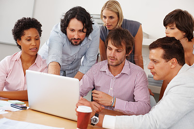 Buy stock photo Young business man pointing at laptop screen to team mates