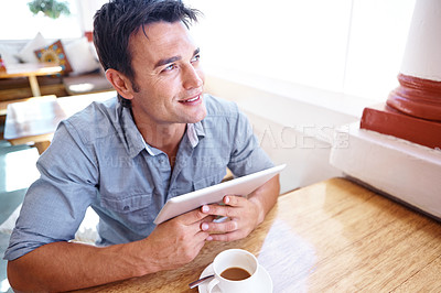 Buy stock photo Shot of a happy man sitting in a cafe holding a touchscreen with a cup of coffee beside him