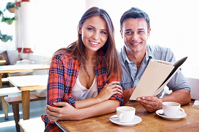 Buy stock photo Portrait of a smiling couple choosing something on a cafe menu with copyspace