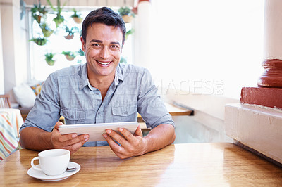 Buy stock photo A handsome young man using a digital tablet in a coffee shop