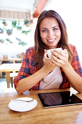 Buy stock photo Portrait of a smiling woman sitting in a coffee shop with a touchscreen and holding a cup of tea