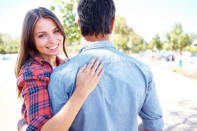 Buy stock photo Shot of a smiling woman hugging her boyfrend