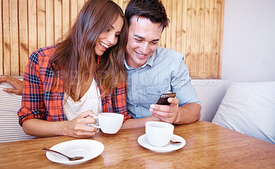 Buy stock photo Shot of a couple on a coffee date looking at a cell phone together with copyspace