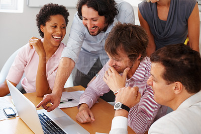 Buy stock photo Handsome business man pointing at laptop with his team in board room