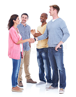 Buy stock photo Coworkers in a multiethnic group meeting each other and shaking hands while isolated on white