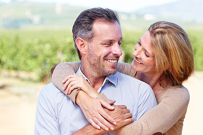Buy stock photo A mature woman embracing her husband while standing on a wine farm