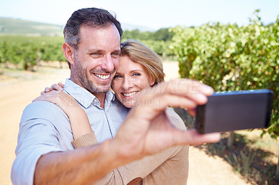 Buy stock photo A mature couple smiling while taking a self-portrait in a vineyard