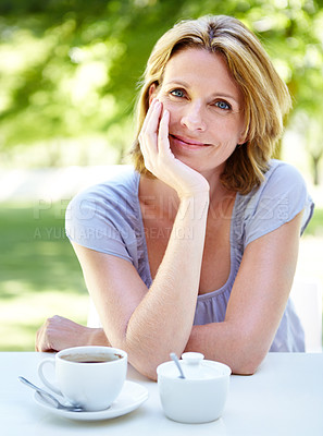 Buy stock photo A happy mature woman sitting in a garden cafe