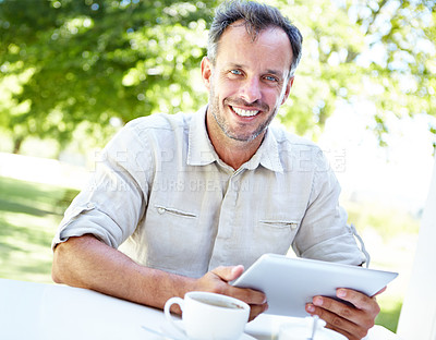Buy stock photo A happy mature man sitting in a garden cafe and using a digital tablet