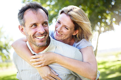 Buy stock photo A happy mature man piggybacking his loving wife around in the park