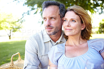 Buy stock photo A mature couple relaxing in the park while sharing a picnic