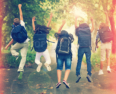 Buy stock photo Rearview shot of a group of school children jumping in the air