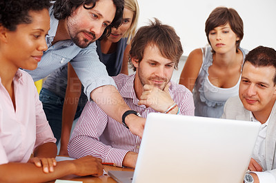 Buy stock photo Young male executive pointing at laptop with his team in meeting room