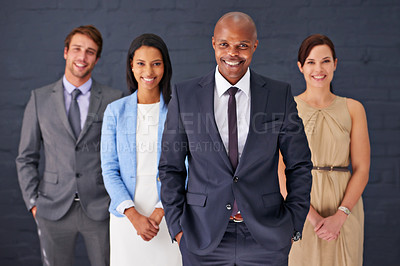 Buy stock photo Portrait of a group of confident businesspeople standing against a gray background