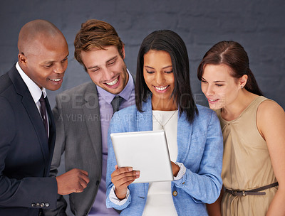 Buy stock photo Shot of a group of businesspeople working over a digital tablet