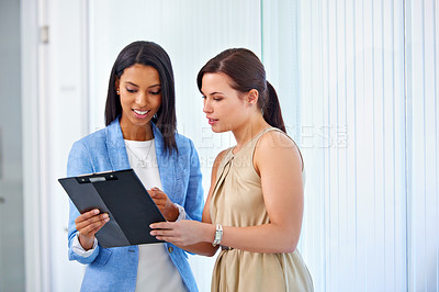 Buy stock photo Shot of a two young businesswomen discussing paperwork