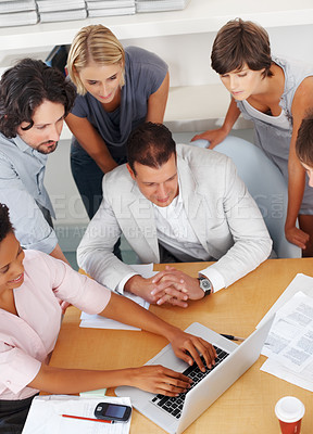 Buy stock photo Business woman working on laptop with team looking at her work