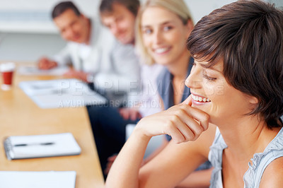 Buy stock photo Happy young woman smiling while colleagues looking at her