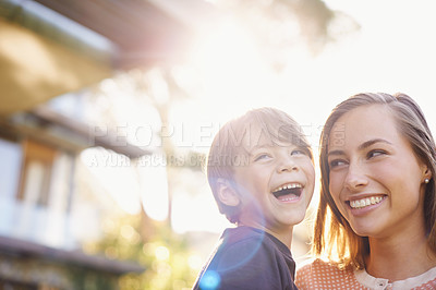 Buy stock photo Shot of a young mother holding her happy son outside