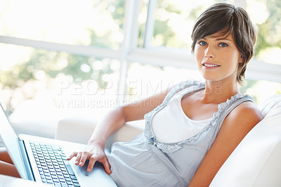 Buy stock photo Beautiful young woman sitting on sofa with laptop
