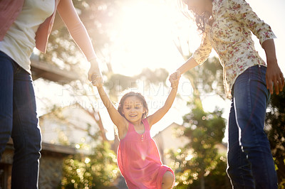 Buy stock photo A cute little girl being swung by her mother and grandmother in the garden