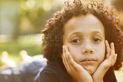 Buy stock photo A solemn little boy lying on the grass with his head in his hands