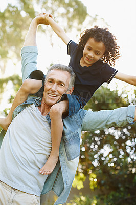 Buy stock photo A grandfather playing with his grandson in the park