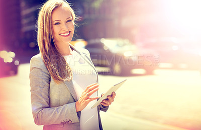 Buy stock photo Portrait of an attractive woman using a digital tablet while walking in the city