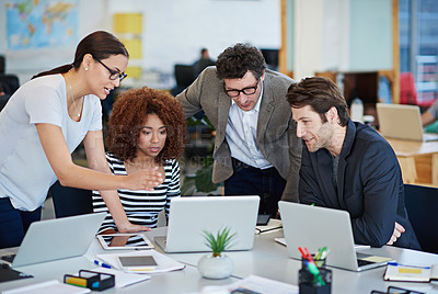 Buy stock photo Cropped shot of business people working on laptops around a table