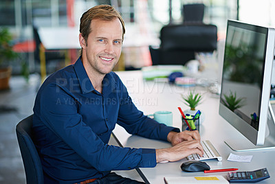 Buy stock photo Portrait of a handsome designer sitting at his workstation in an office