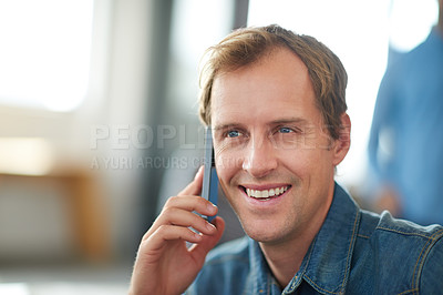 Buy stock photo Shot of a man sitting in an office talking on a cellphone with colleagues in the background