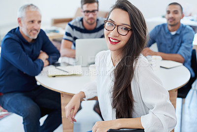 Buy stock photo Portrait of a young office worker sitting at a table with colleagues in the background
