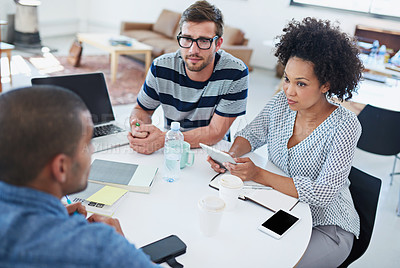 Buy stock photo Shot of coworkers talking over a digital tablet